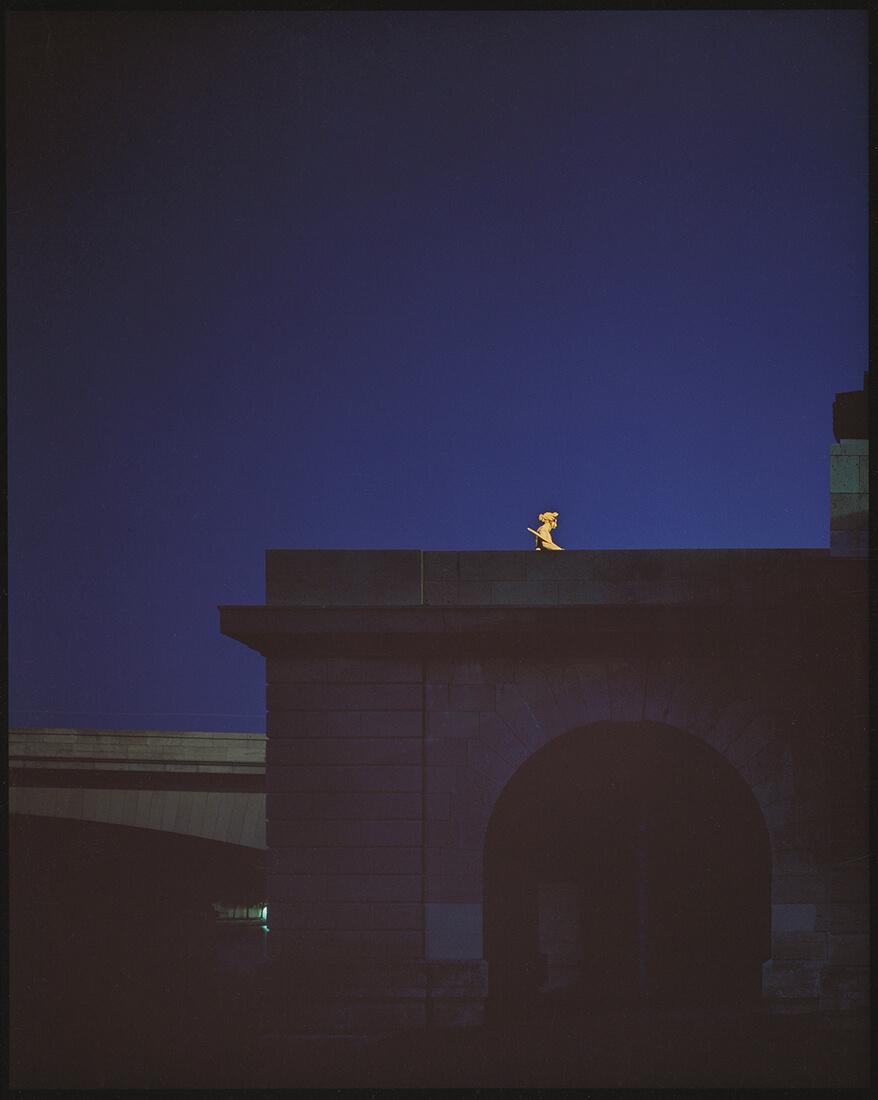 Vue nocturne d'une pile de pont et d'une statue illuminée