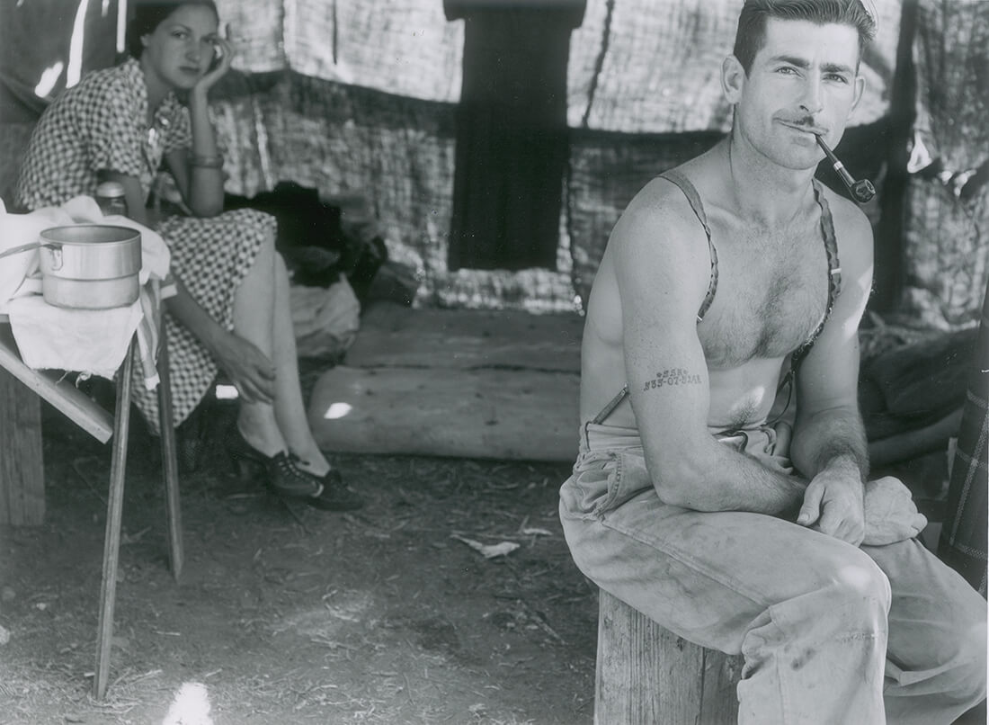 Unemployed lumber worker goes with his wife to the bean harvest. Note social security number tattooed on his arm. Oregon