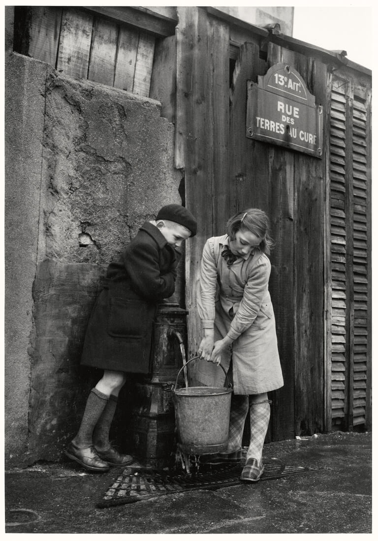 Enfants prenant de l'eau à la fontaine, rue des Terres-au-Curé